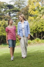 Smiling mother having a walk with her daughter in a park on a summers day