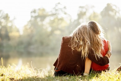 Hugging women on grass
